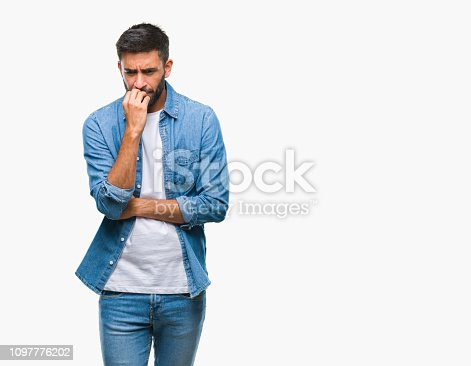 Adult hispanic man over isolated background looking stressed and nervous with hands on mouth biting nails. Anxiety problem.