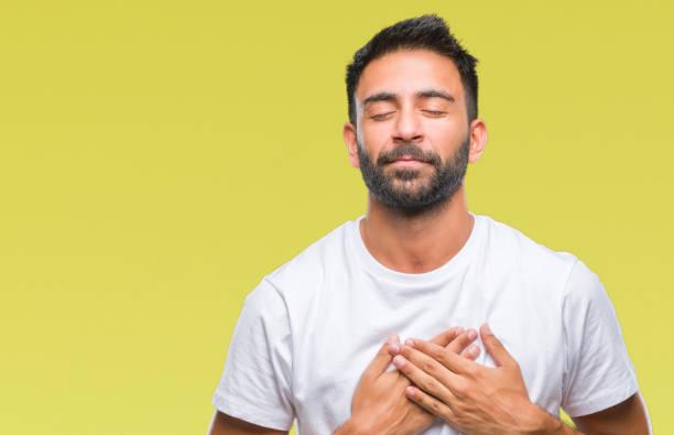 erwachsenen hispanic mann über isolierte hintergrund lächelnd mit händen auf brust mit geschlossenen augen und dankbar geste auf gesicht. gesundheitskonzept. - die wahrheit tut weh stock-fotos und bilder