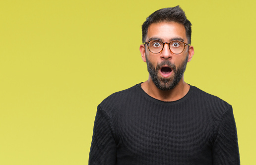istock Adult hispanic man wearing glasses over isolated background afraid and shocked with surprise expression, fear and excited face. 1042788932