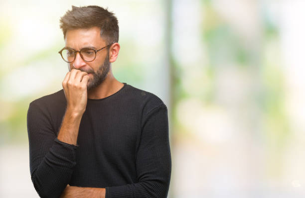 Adult hispanic man wearing glasses over isolated background looking stressed and nervous with hands on mouth biting nails. Anxiety problem. Adult hispanic man wearing glasses over isolated background looking stressed and nervous with hands on mouth biting nails. Anxiety problem. worried stock pictures, royalty-free photos & images