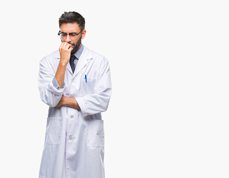 istock Adult hispanic scientist or doctor man wearing white coat over isolated background looking stressed and nervous with hands on mouth biting nails. Anxiety problem. 1050899722