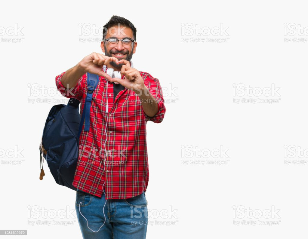 Adult hispanic student man wearing headphones and backpack over isolated background smiling in love showing heart symbol and shape with hands. Romantic concept. stock photo