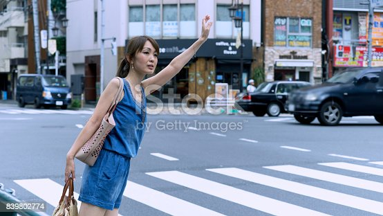 istock Adult Japanese woman standing by a street and waiting for a taxi in Tokyo. 839802774