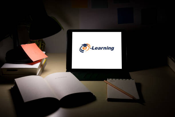 Adult learners and university student watching lesson online on tablet and studying from home at night. Online study and working from home concept during COVID-19 pandemic. stock photo