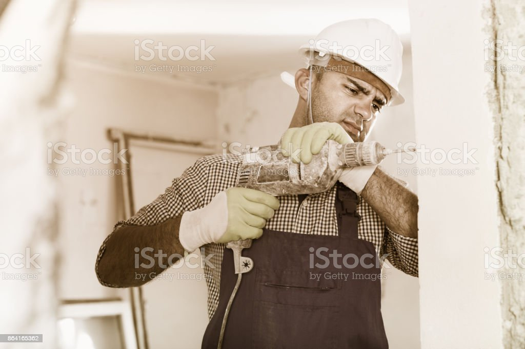 Adult male builder renovating with drill in gloves royalty-free stock photo