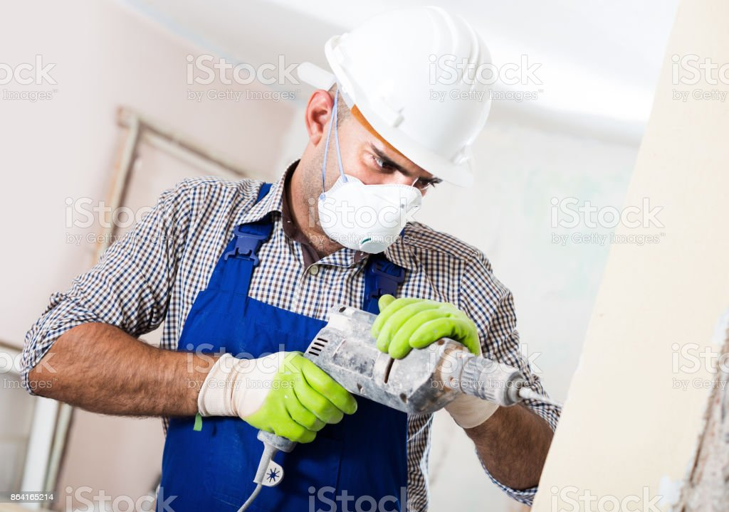 Adult male builder renovating with drill in mask royalty-free stock photo