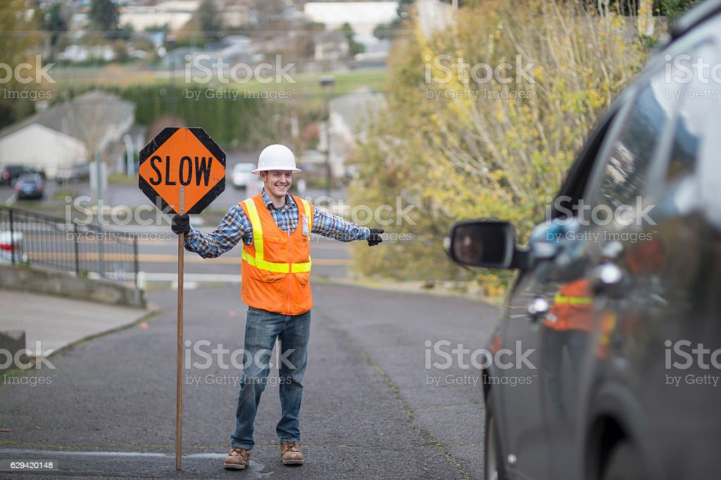 Adult male construction worker directing traffic stock photo