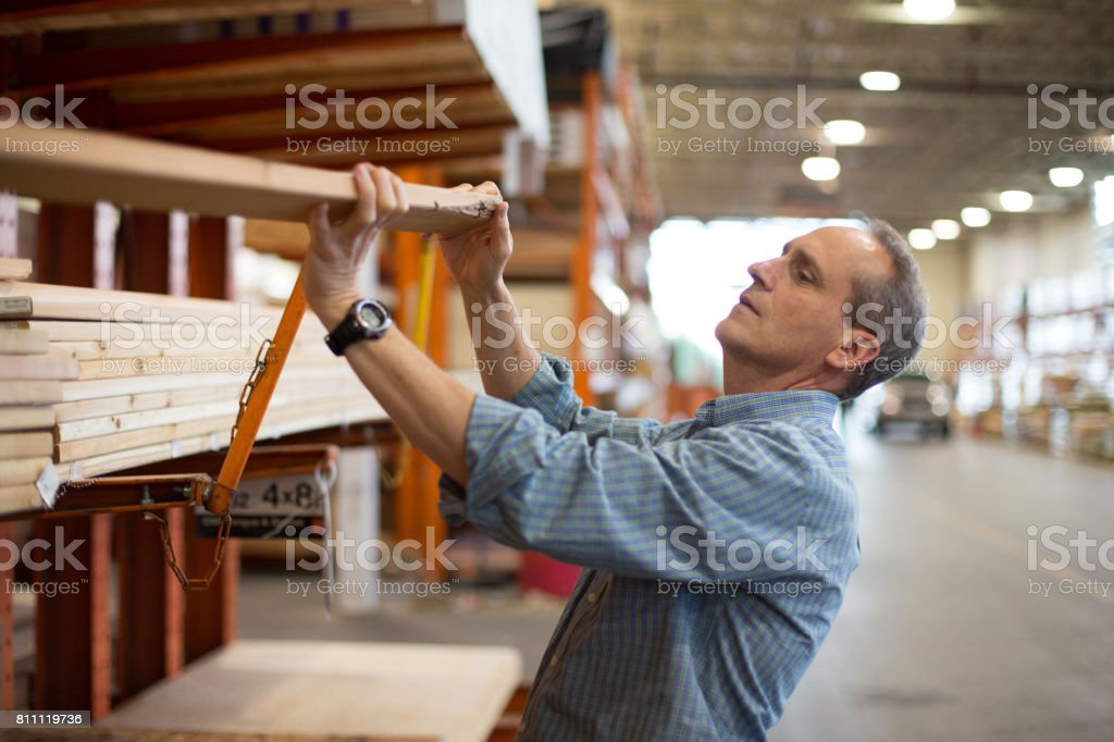Adult male customer in hardware store choosing lumber stock photo