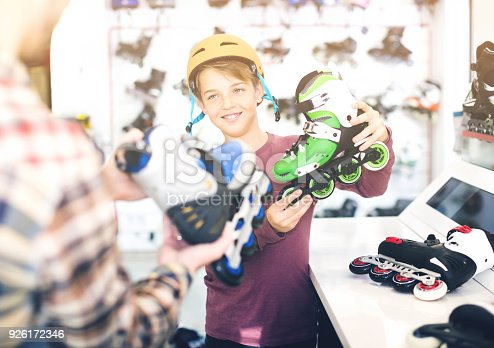 istock Adult male demonstrating roller-skates to boy 926172346