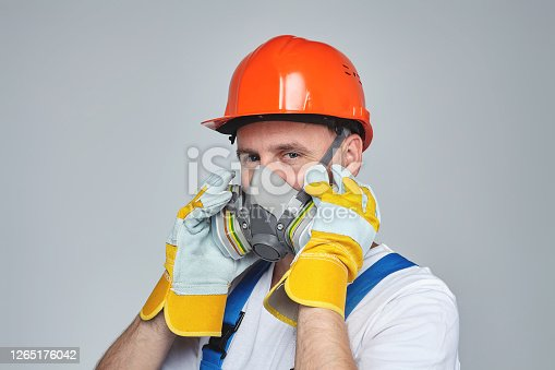 adult male in a construction helmet and a respirator. photo session in the Studio on a white background. concept of construction services.