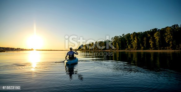 Adult male paddling a kayak on a river at sunset