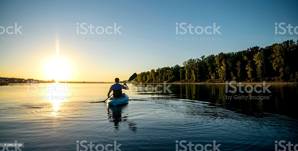 Adult male paddling a kayak on a river at sunset stock photo