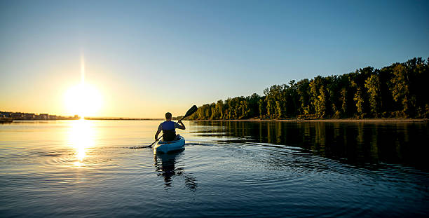 adult male paddling a kayak on a river at sunset - caiaque - fotografias e filmes do acervo