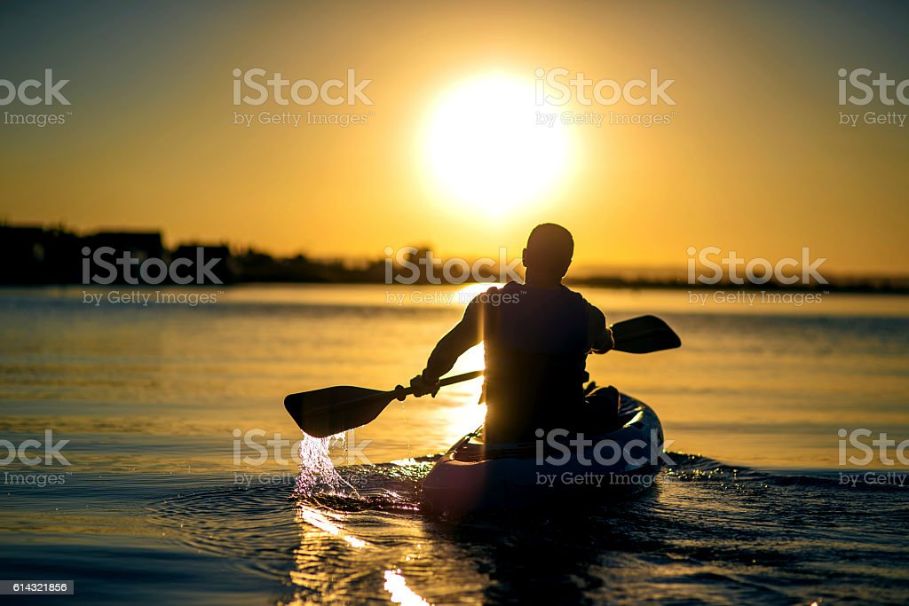 Adult male paddling a kayak on a river into the sunset - Photo