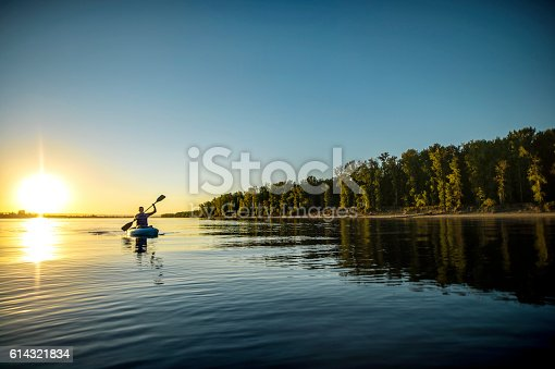 Adult male paddling in a kayak on a river next to shore