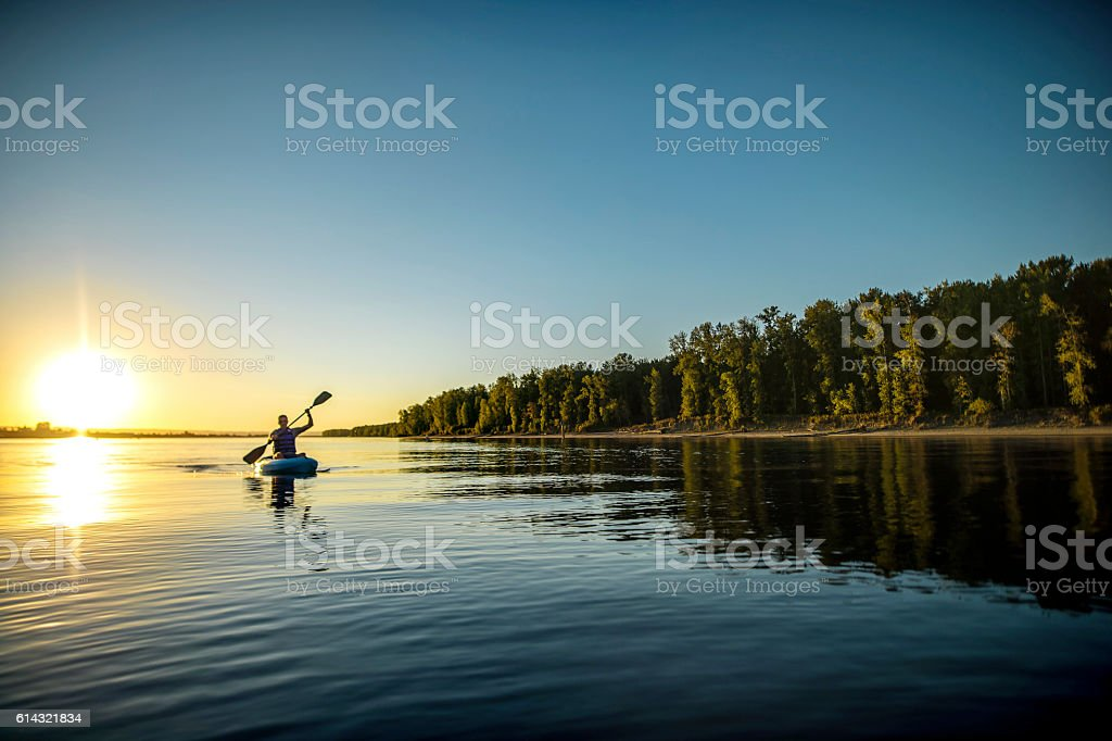 Adult male paddling in a kayak on a river next to - foto de stock