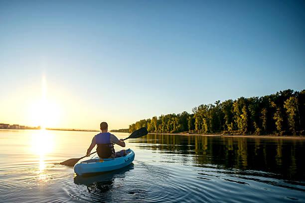 adult male paddling in a single kayak wearing a lifejacket - caiaque canoagem e caiaque - fotografias e filmes do acervo