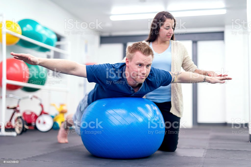 Adult male patient balancing on a therapy exercise ball stock photo