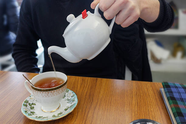 adult male pouring tea from teapot - jasmin party stock-fotos und bilder