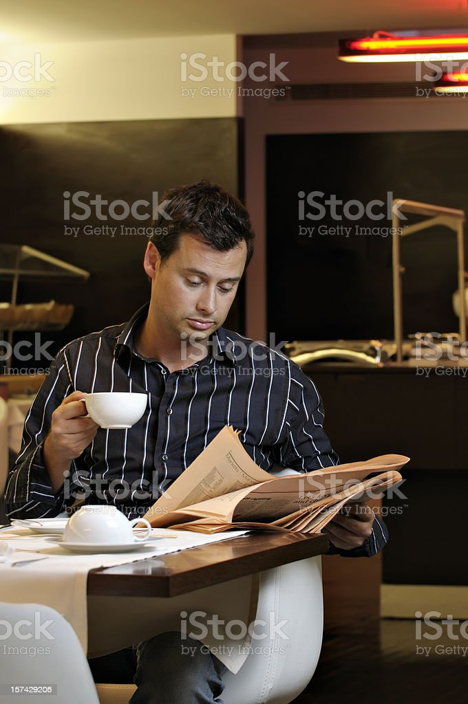 Adult male reading the newspaper during breakfast royalty-free stock photo