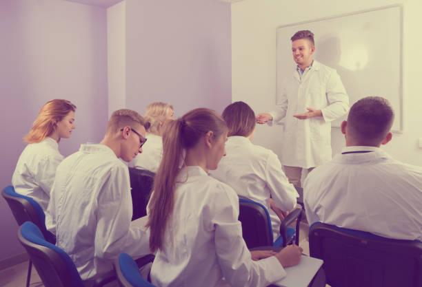 erwachsenen männlichen studenten, die in der nähe von whiteboard zu beantworten - lautsprecher test stock-fotos und bilder