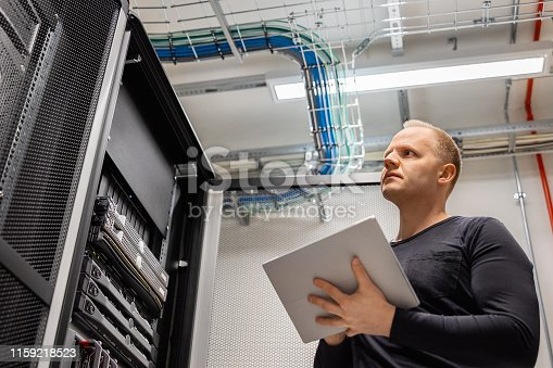 istock Adult Male Technician Holding Digital Tablet and Analysing Servers in Datacenter 1159218523