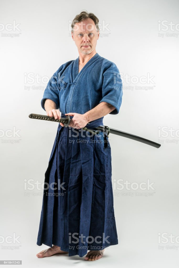 Adult male training Iaido about to draw a Japanese sword. stock photo