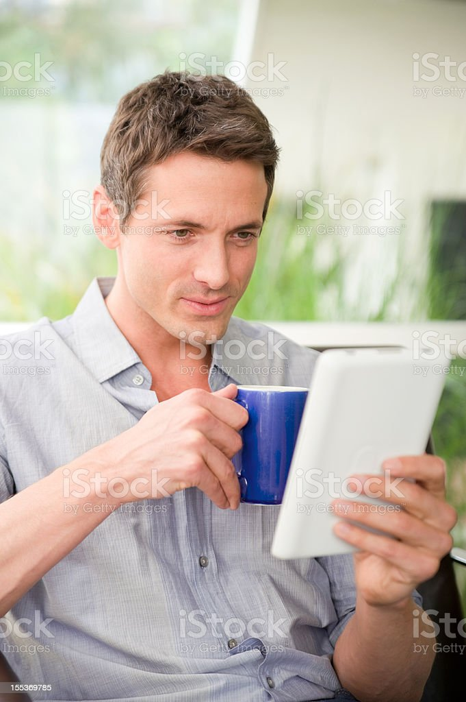Adult male using an e-reader royalty-free stock photo