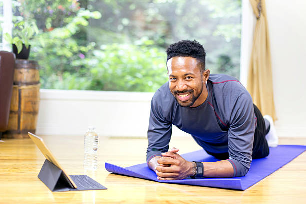 adult male using smart tablet to guide workout and smiling - yoga videos stock-fotos und bilder