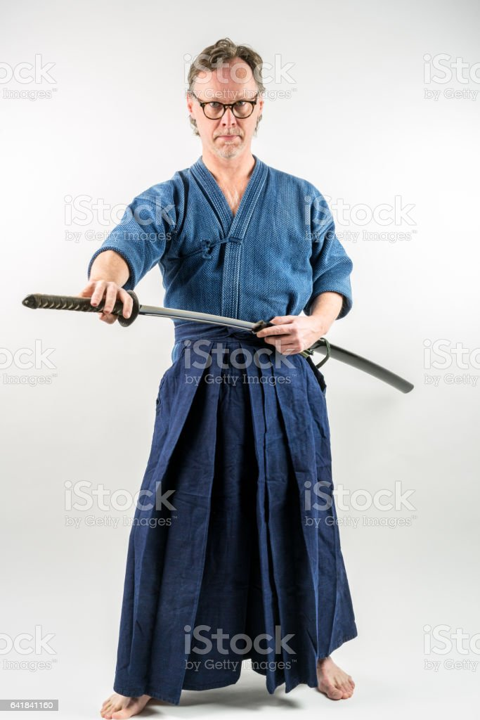 Adult male with glasses training Iaido drawing a Japanese sword. stock photo