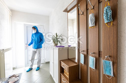 istock Adult Man Arriving Home With Protective Mask on Face 1221222232