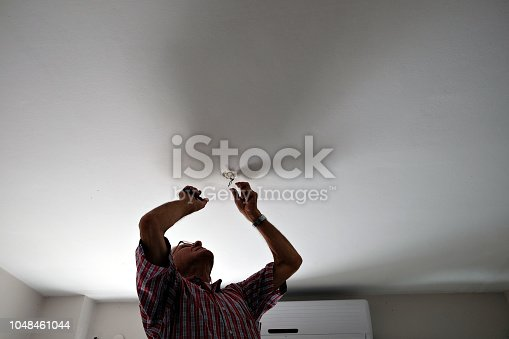 istock Adult man assembling electricity after moving 1048461044