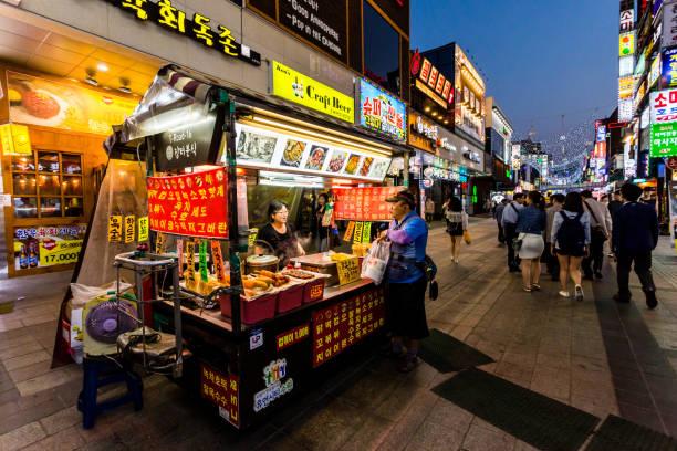 Adult man buying fast food at main street in Suwon. Street food is very popular in Korea. You can buy kimbap, teokbokki, bibimbap, kimchi. Suwon, South Korea - June 14, 2017: Adult man buying fast food at main street in Suwon. Street food is very popular in Korea. You can buy kimbap, teokbokki, bibimbap, kimchi. asian market stock pictures, royalty-free photos & images