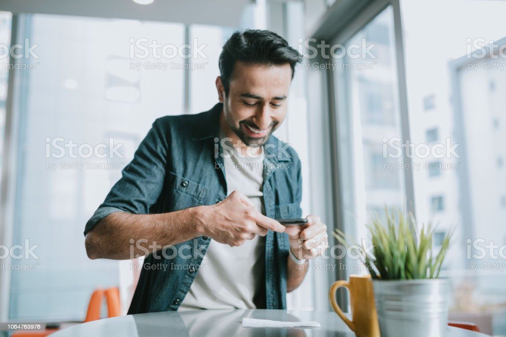 Adult Man Depositing Check With Smartphone stock photo