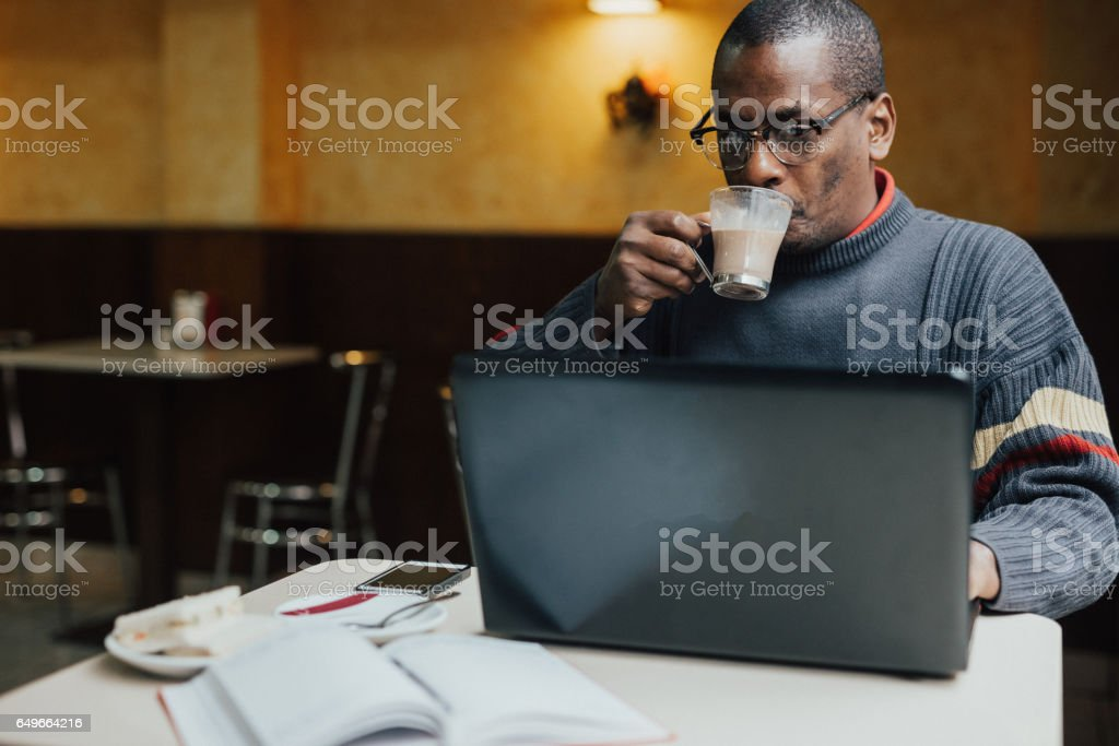 Adult man drinking coffee and surfing the net stock photo