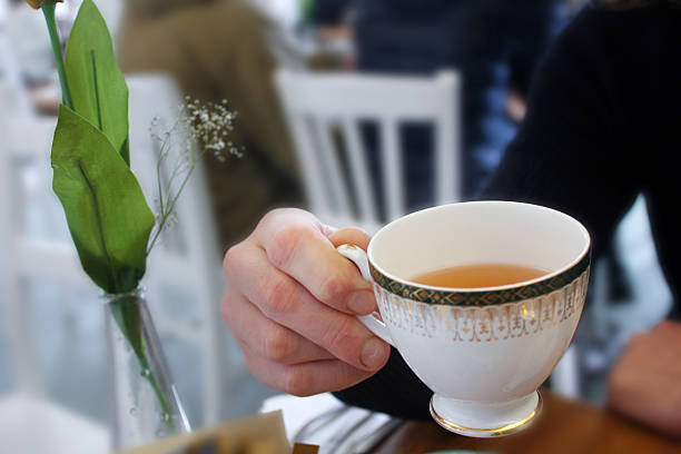adult man drinking hot tea in cafe - jasmin party stock-fotos und bilder
