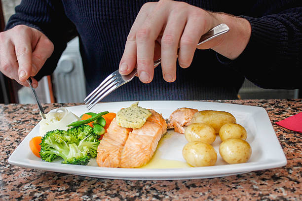 adult man eating salmon steak and vegetables - lax på gaffel man ej pasta bildbanksfoton och bilder