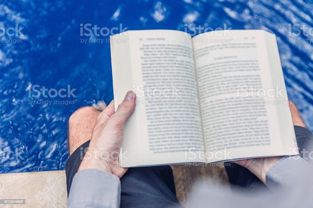 Adult man enjoy reading book beside swimming pool stock photo
