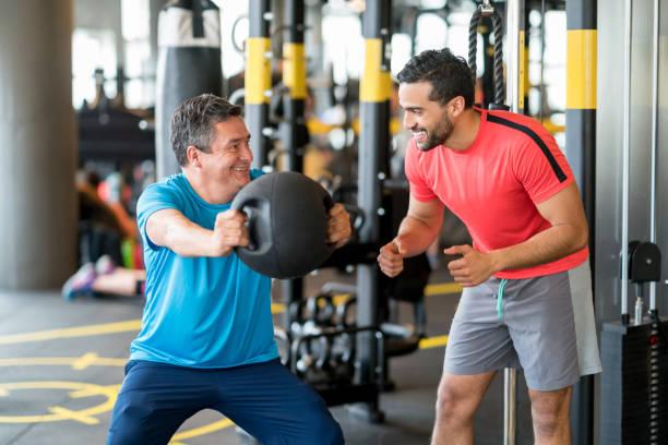 Hombre adulto, hacer ejercicio en el gimnasio con un entrenador personal - foto de stock