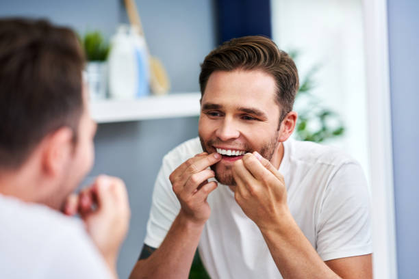 Erwachsene Mann Zahnseide Zähne im Badezimmer – Foto