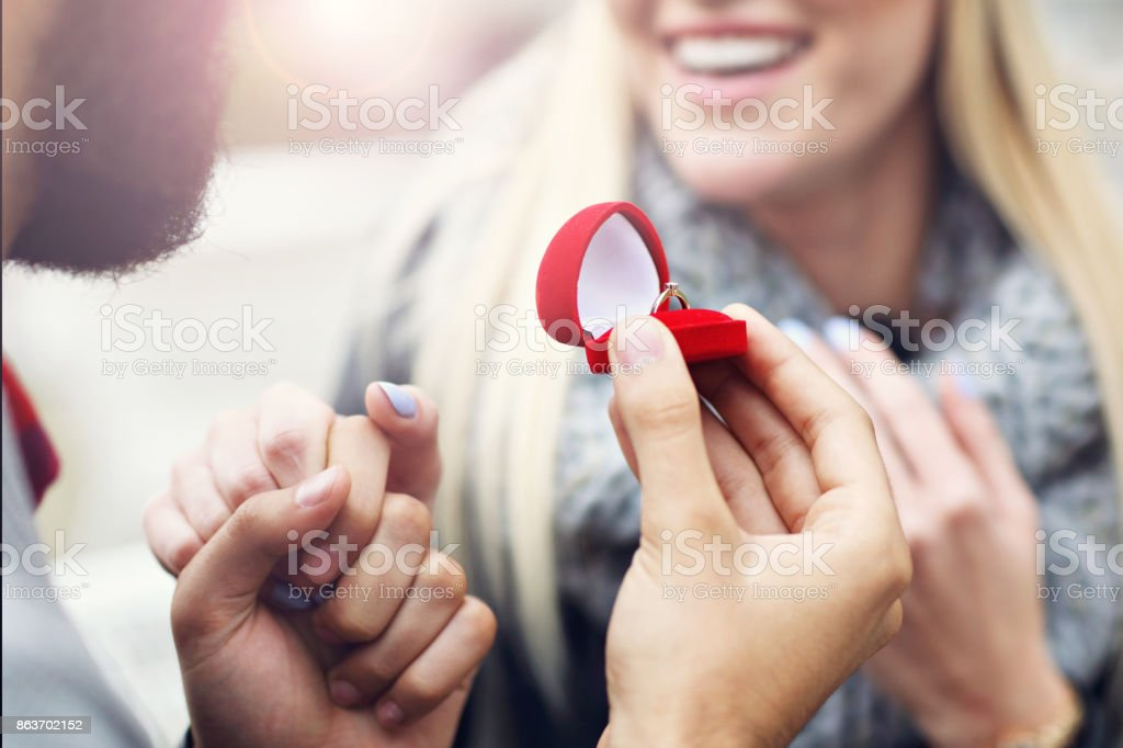 Adult man giving engagement ring to beautiful woman stock photo