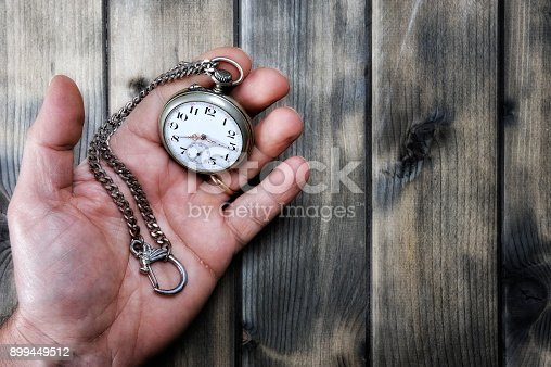 istock Adult man holding an antique pocket watch in his hand 899449512