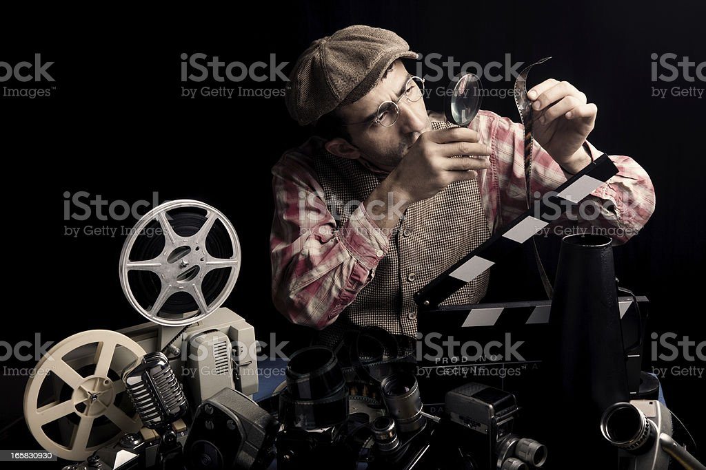 Adult Man Holding Cinema Film And Checking With Magnifying Glass stock photo