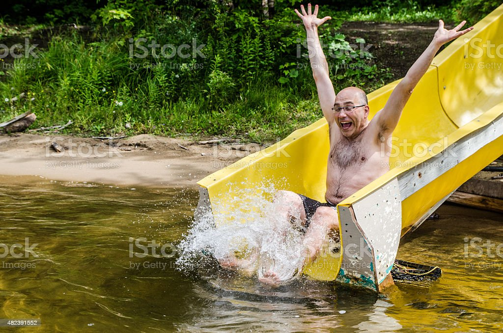 Adult man in a water slide stock photo