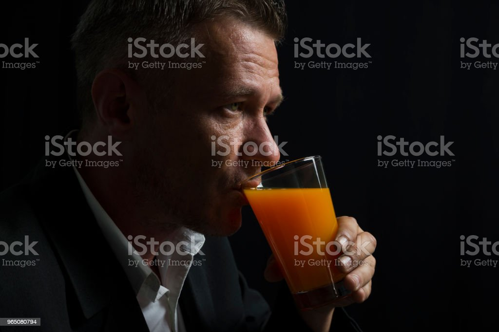 Adult man in black suit drinking juice in front of black curtain zbiór zdjęć royalty-free