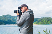 Adult man in hoodie walking around lake with DSLR camera ans shooting, beautiful summer day, half body portrait, landscape photography concept