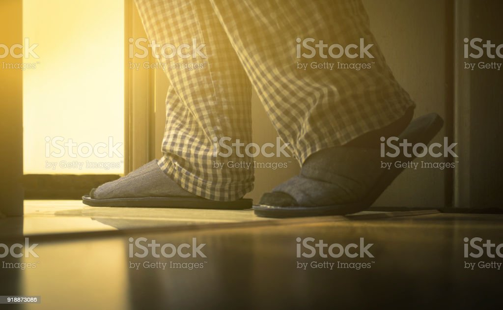 Adult man in pijamas walks to a bathroom at the night. Men's healths concept. Toned stock photo