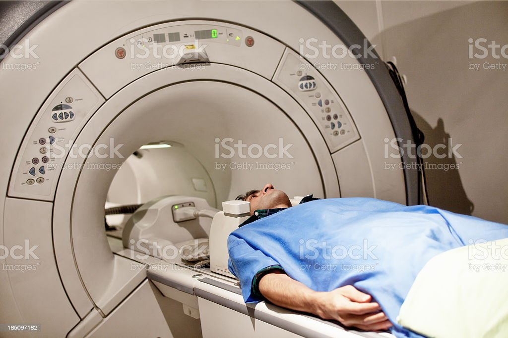 Adult Man In Protective Hospital Clothes Having MRI Scan stock photo