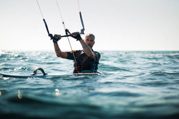 erwachsener mann im meer mit einem drachen und einem brett - kitesurfen lernen stock-fotos und bilder