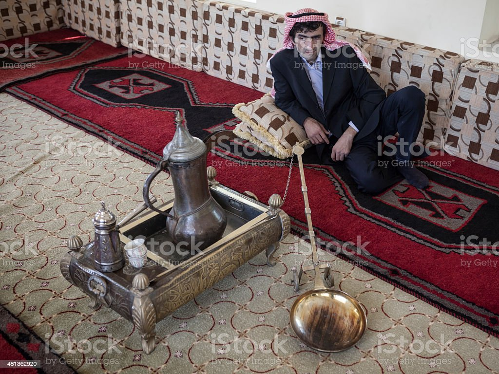 Adult man in traditional arabic clothes sitting on handmade carpet stock photo